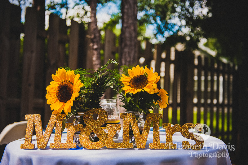 sunflower centerpieces and gold glitter Mr and Mrs sign at backyard wedding   Elizabeth Davis Photography